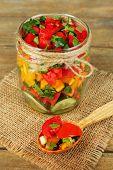 Vegetable salad in glass jar, on sackcloth napkin, on wooden background