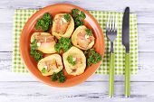 Baked potato with bacon on plate, on wooden background