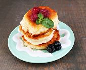 Tasty pancakes with fresh berries, cream and mint leaf on plate, on wooden background