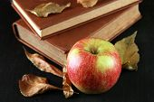 Apple with books and dry leaves on wooden background