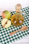 Apple cider vinegar in glass bottle and ripe fresh apples, on wooden table