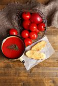Homemade tomato juice in color mug, toasts and fresh tomatoes on wooden background