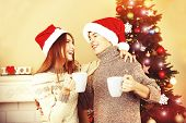 Nice love couple sitting with mugs in front of fireplace near Christmas tree. Woman and man celebrating Christmas