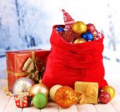 Red bag with Christmas toys on winter background