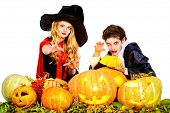 Boy and girl teenagers wearing halloween costumes posing with pumpkins. Isolated over white. Autumn holidays.