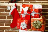 Christmas presents on chair on brown brick wall background