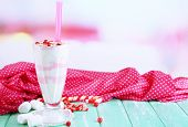 Cranberry milk shake in glass, on color wooden background