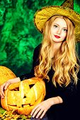Pretty blonde girl teenager in a costume of witch posing with pumpkins over dark smoky background. Halloween.