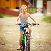 happy little girl riding a bicycle in rural areas