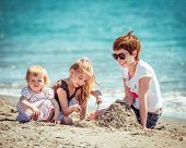 happy family: mother and two cute daughters playing in the sand on the sea shore