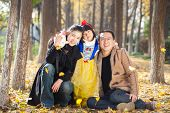 happy family togetherness portrait in forest, father,mother and daughter.