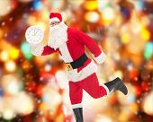 christmas, holidays and people concept - man in costume of santa claus running with clock showing twelve over red lights background