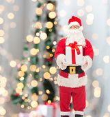 christmas, holidays and people concept - man in costume of santa claus with gift box over tree lights background