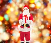 christmas, holidays and people concept - man in costume of santa claus with gift box over red lights background