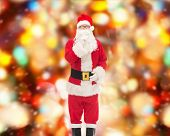 christmas, holidays and people concept - man in costume of santa claus making hush gesture over red lights background