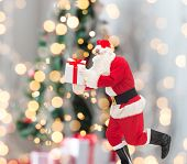 christmas, holidays and people concept - man in costume of santa claus running with gift box over tree lights background