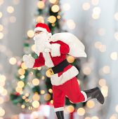christmas, holidays and people concept - man in costume of santa claus running with bag over tree lights background