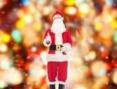 christmas, holidays, gesture and people concept- man in costume of santa claus showing thumbs up over red lights background