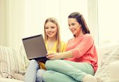 friendship, technology and internet concept - two smiling teenage girls with laptop computer at home