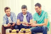 friendship, technology, food and leisure concept - smiling friends taking picture of food with smartphone camera at home