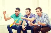 friendship, sports and entertainment - happy male friends with vuvuzela watching sports at home