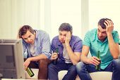 friendship, sports and entertainment concept - sad male friends with beer watching sports on tv at home