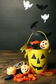 Different sweets for Halloween party on wooden table, on dark background