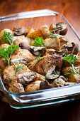 Tasty baked chicken legs with potatoes, mushrooms and herbs