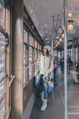 stock photo of tram  - Beautiful young woman wearing ecological fur poses on a tram - JPG