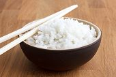 stock photo of chopsticks  - Rustic bowl of white rice on modern wood surface - JPG