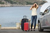 stock photo of breakdown  - Worried traveler woman calling assistance with a breakdown car on the beach with the sea in the background - JPG