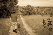 foto of wander  - Wanderer walking a sandy path with a suitcase in monochrome - JPG