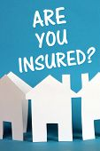 stock photo of disaster preparedness  - The question Are You Insured above a chain of white paper houses on a blue background - JPG