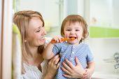 stock photo of tooth  - mother teaching son child teeth brushing in bathroom - JPG