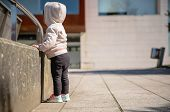 foto of hoodie  - Little girl with sneakers and hoodie standing in a city square on a sunny day - JPG