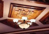 stock photo of chandelier  - Beautiful retro chandelier on wooden ceiling closeup  - JPG
