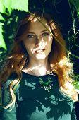 image of auburn  - Beautiful young caucasian woman with auburn hair freckles and green eyes hiding behind the vine branch - JPG