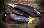 picture of brinjal  - Fresh eggplants with leaves over dark wooden background - JPG