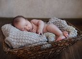 foto of rest-in-peace  - One month old baby boy in the basket on the wooden floor - JPG