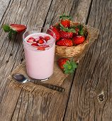 stock photo of yogurt  - Fresh yogurt in a glass with strawberries on a old rustic wooden table - JPG