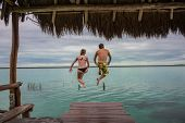 stock photo of dock a lake  - Jumping at Bacalar Lake at Riviera Maya Quinatana Roo - JPG