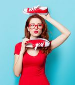 picture of redhead  - Surprised redhead girl in red dress with gumshoes on blue background - JPG