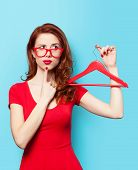 stock photo of redhead  - Surprised redhead girl with hanger on blue background - JPG