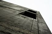foto of orifice  - Concrete wall with window openings of the unfinished building against the white sky - JPG