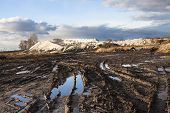 picture of boggy  - Mud and puddles on the dirt road with sand hills in the background - JPG