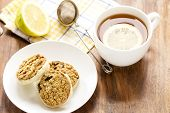 stock photo of baked raisin cookies  - 3 oatmeal raisin cookies on white plate and cup of tea with lemon slice in it - JPG