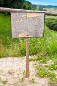 stock photo of ravines  - Empty old wooden sign with place for text stands on the edge of the ravine - JPG