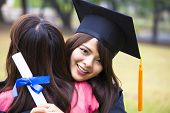 stock photo of graduation  - young female graduate hugging her friend at graduation ceremony - JPG