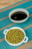 stock photo of soy sauce  - Bowl with soy sauce and soy beans on a bamboo mat - JPG