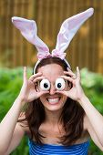 pic of bunny ears  - A portrait of a woman making a funny expression wearing Easter bunny ears holding up silly eyes made from eggs in front of her eyes outside in a garden during the spring season - JPG